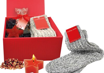 """Dovana """"Patogumas"""". Raudona kartoninė dėžutė, kurioje rasite  viską, ko jums reikia patogiai žiemos vakarui (žvakutė, šiltos koinės, arbata)."""